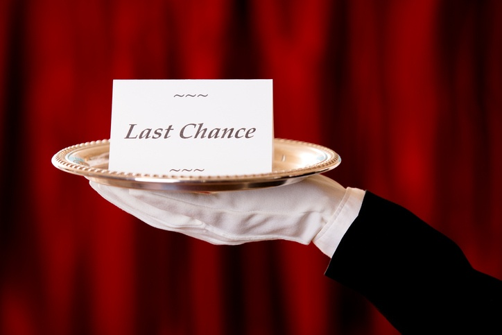 White gloved hand in black suit holds a blank notecard on a silver platter.  Red curtains background.  See more like this image with numerous notecard messages, backgrounds in lightbox below.