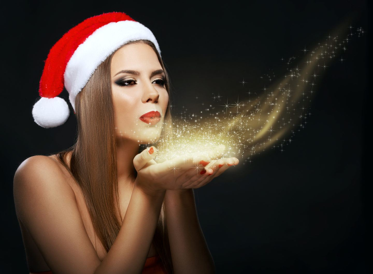 Beautiful woman portrait with Santa's hat, blowing golden dust