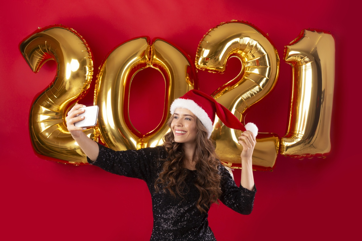 Elegant lady in Santa hat and sexy dress taking selfie on New Year's eve 2021, red background. Panorama