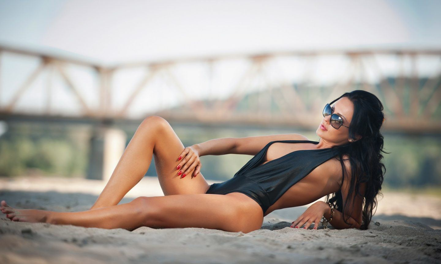 Portrait of young sexy brunette girl in black low-cut swimsuit lying on the beach with a bridge in background. Sensual attractive woman with sunglasses and perfect body relaxing on the beach.